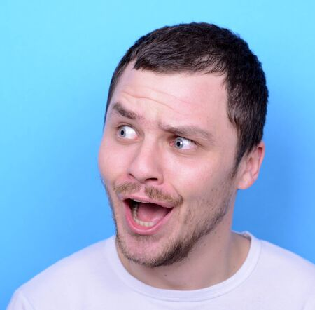 weirdo: Portrait of man with funny face against blue background