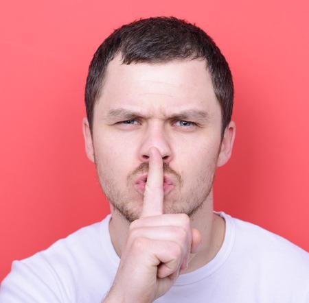 discreto: Retrato de hombre con gesto de silencio contra el fondo rojo Foto de archivo