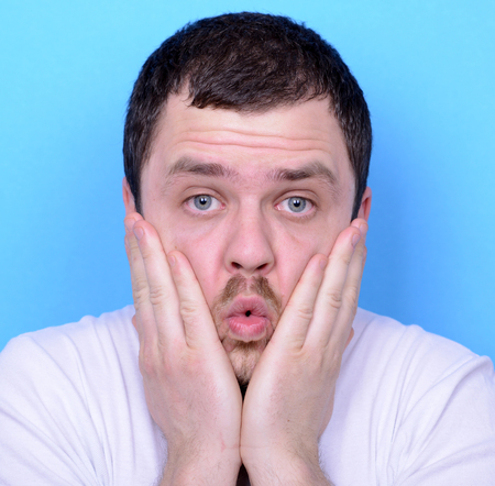 weirdo: Portrait of man with dusgusted gesture against blue background