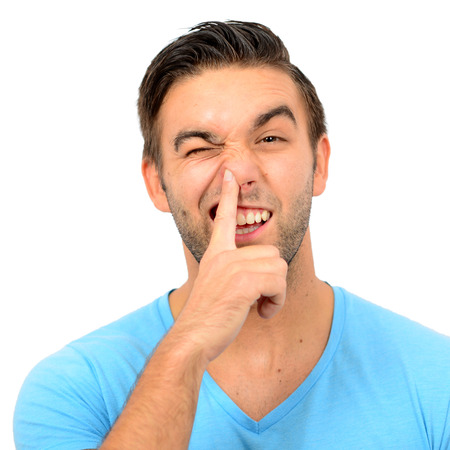 nariz: Retrato de un chico divertido con el dedo en la nariz contra el fondo blanco Foto de archivo