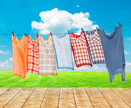 Laundry hanging over flower field with wooden floor Stock Photo
