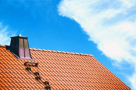 Toit de la maison contre le ciel bleu et lumineux
