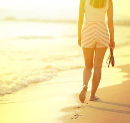 huellas pies: recorrido de la playa - mujer que camina en la playa de arena dejando huellas en la arena. Detalle del primer de pies femeninos y playa de arena dorada
