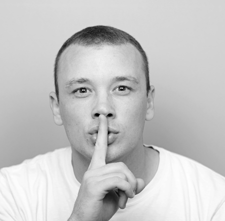 conspiratorial: Portrait of man with gesture for silence against green background