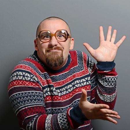 manos aplaudiendo: Retrato de un empoll�n aplaudiendo las manos con los vidrios y su�ter retro contra el fondo gris