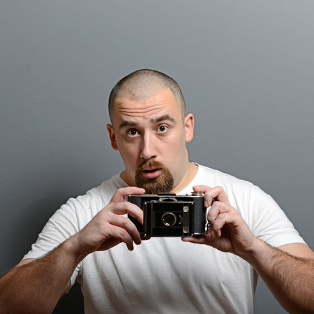 stumped: Portrait of a man holding retro camera against gray background Stock Photo