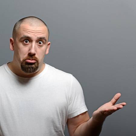 ambiguous: Portrait of a confused man against gray background