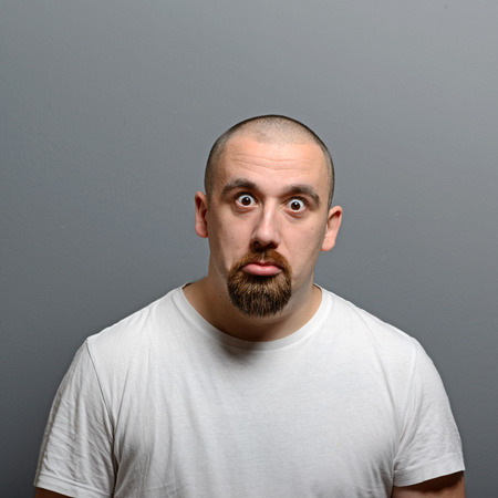 stumped: Portrait of a confused man against gray background