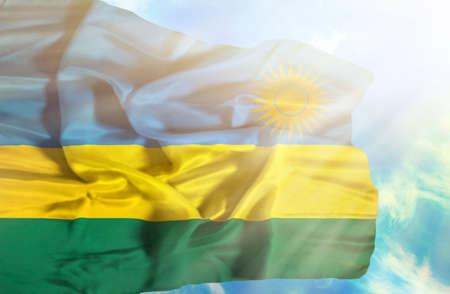 rwanda: Rwanda waving flag against blue sky with sunrays