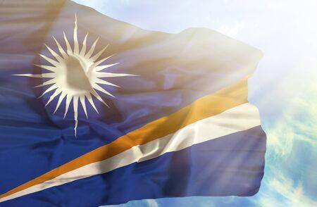 marshall: Marshall Islands waving flag against blue sky with sunrays