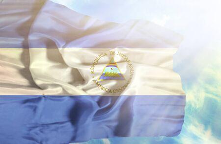 nicaragua: Nicaragua waving flag against blue sky with sunrays Stock Photo