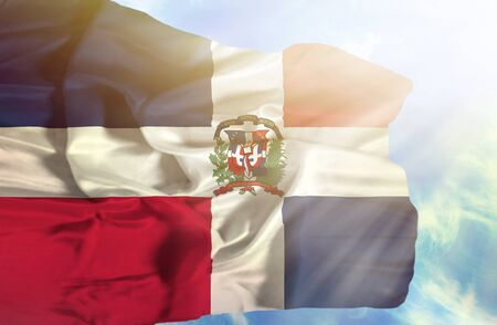 dominican republic: Dominican Republic waving flag against blue sky with sunrays Stock Photo