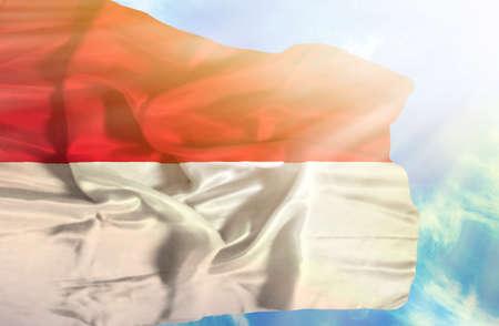 monaco: Monaco waving flag against blue sky with sunrays