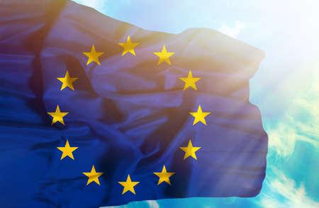 European Union waving flag against blue sky with sunrays Stock Photo