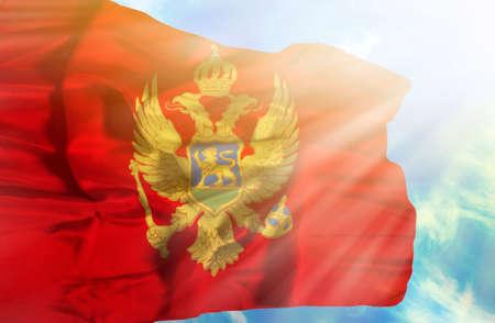 montenegro: Montenegro waving flag against blue sky with sunrays Stock Photo