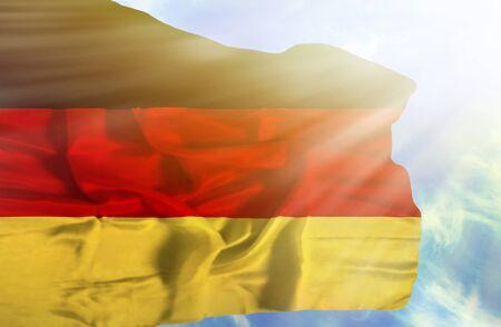 deutchland: Germany waving flag against blue sky with sunrays