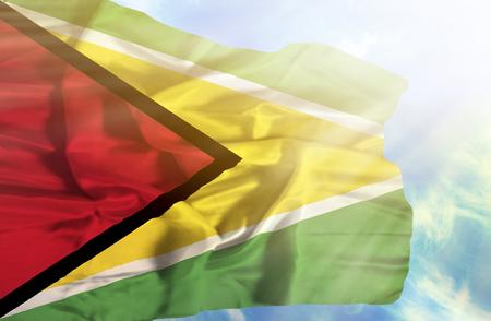 sunrays: Guyana waving flag against blue sky with sunrays