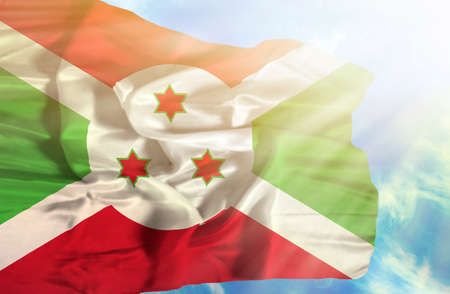sunrays: Burundi waving flag against blue sky with sunrays