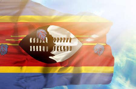 sunrays: Swaziland waving flag against blue sky with sunrays