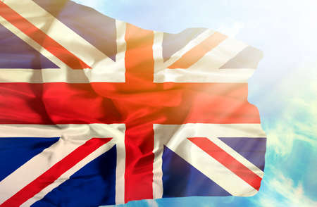 grunge union jack: Great Britain waving flag against blue sky with sunrays Stock Photo