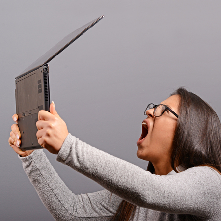 angry computer: Portrait of angry woman screaming at  her laptop against gray background