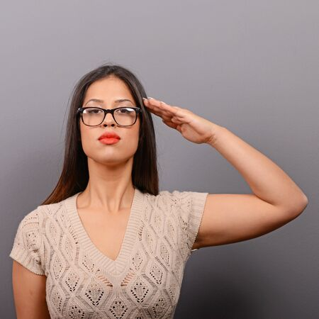 saluting: Portrait of serious woman saluting in casual clothes against gray background Stock Photo