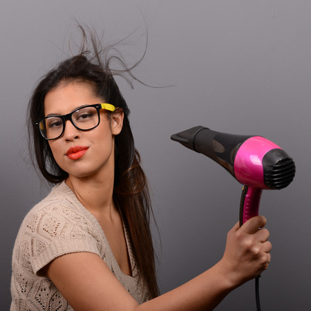blow dry: Portrait of a woman holding hair dryer against gray background Stock Photo