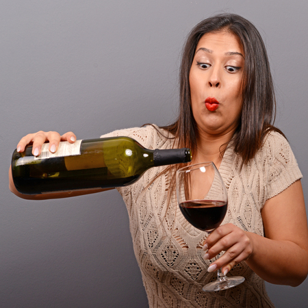 drunk girl: Portrait of woman holding wine bottle and glass against gray background