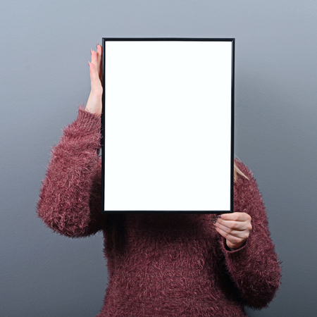 woman hiding: Portrait of woman hiding behind blank sign board