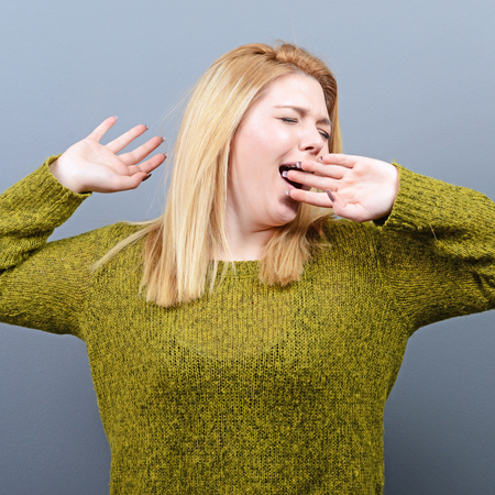 drowsiness: Portrait of young woman stretching and yawning against gray background