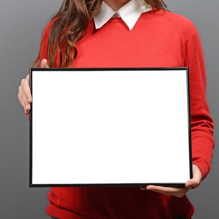 hoja en blanco: Woman holding empty frame with space for your advertisement against gray background