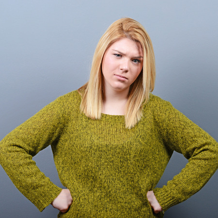 pissed off: Portrait of mad woman against gray background