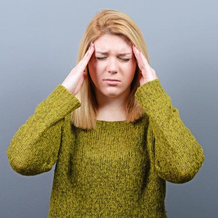 headache: Portrait of woman with headache against gray background Stock Photo
