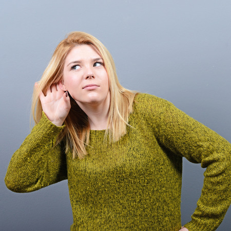 bruit: Portrait of woman trying to listen something against gray background Stock Photo