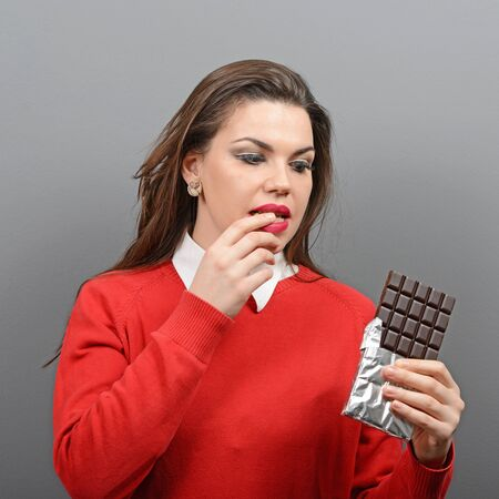 temptation: Beautiful woman in temptation of eaiting a chocolate against gray background