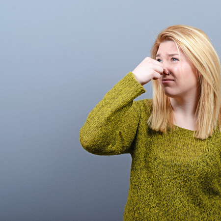 intolerable: Portrait of woman covering nose with hand showing that something stinks against gray background
