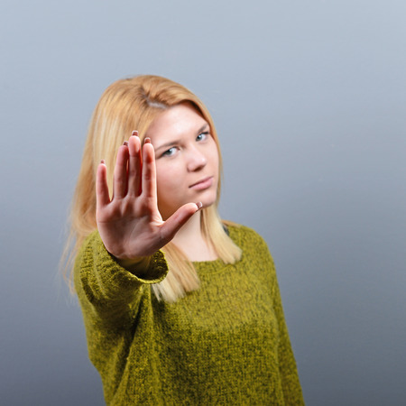 veto: Portrait of woman showing stop with hand against gray background Stock Photo