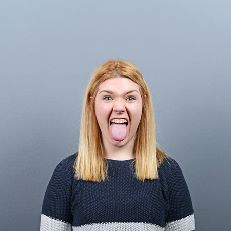 tongue out: Portrait of woman sticking out her tongue against gray background Stock Photo
