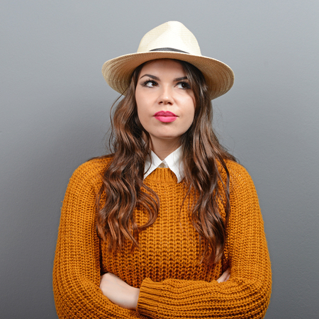 urban people: Portrait of urban looking woman in sweater and hat against gray background