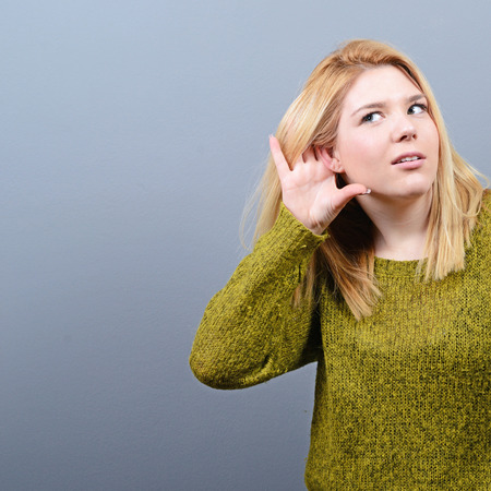 tattle: Portrait of woman trying to listen something against gray background Stock Photo