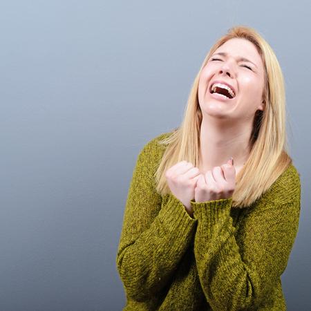 Mujer que ruega por algo o pidiendo clemencia contra el fondo gris