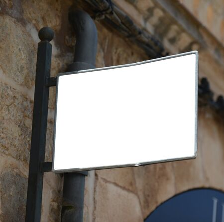 nameboard: Blank metal sign hanging on city wall