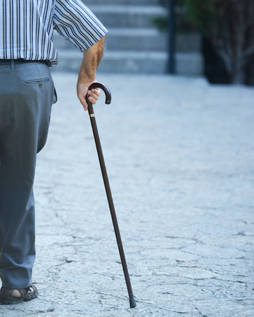puckered: Old man walking with his hands on a wooden walking stick