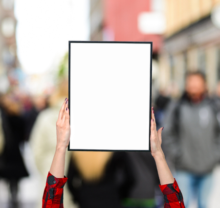 demonstrator: Female hand holding blank boards against city crowd - Woman rights concept