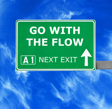 nonchalant: GO WITH THE FLOW road sign against clear blue sky