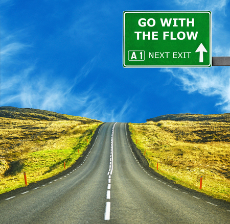 considerate: GO WITH THE FLOW road sign against clear blue sky
