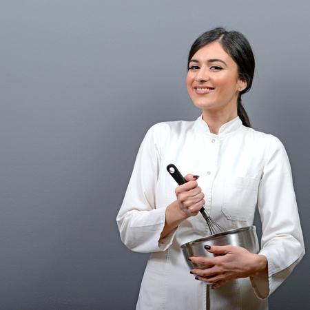 panadero: Retrato de la hermosa mezcla cocinero de la mujer en un cuenco sobre fondo gris