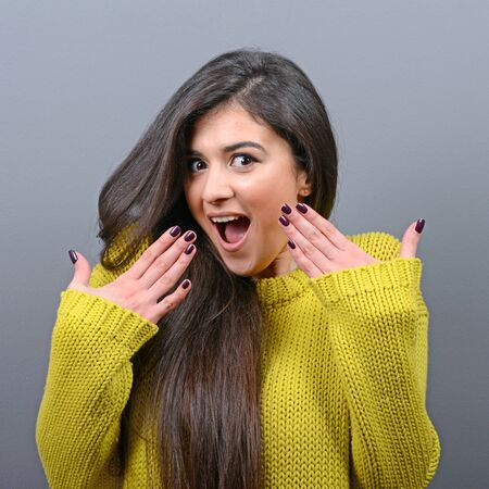 Portrait of a ecstatic woman with spread hands against gray background Stock Photo