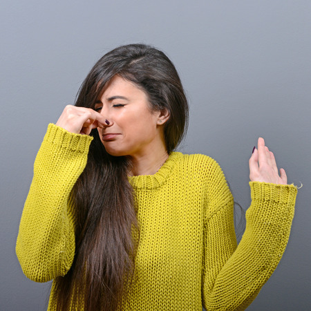 stinks: Portrait of woman covering nose with hand showing that something stinks against gray background