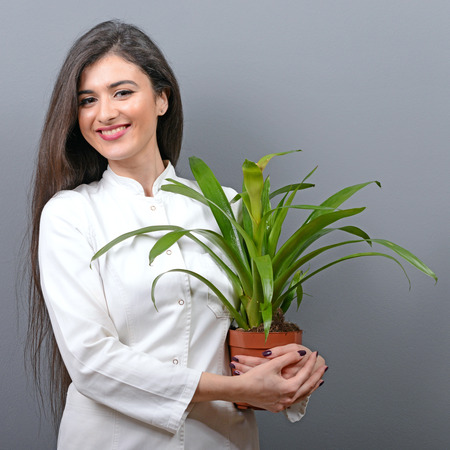 botanist: Portrait of young botanist woman in uniform holding plant against gray background